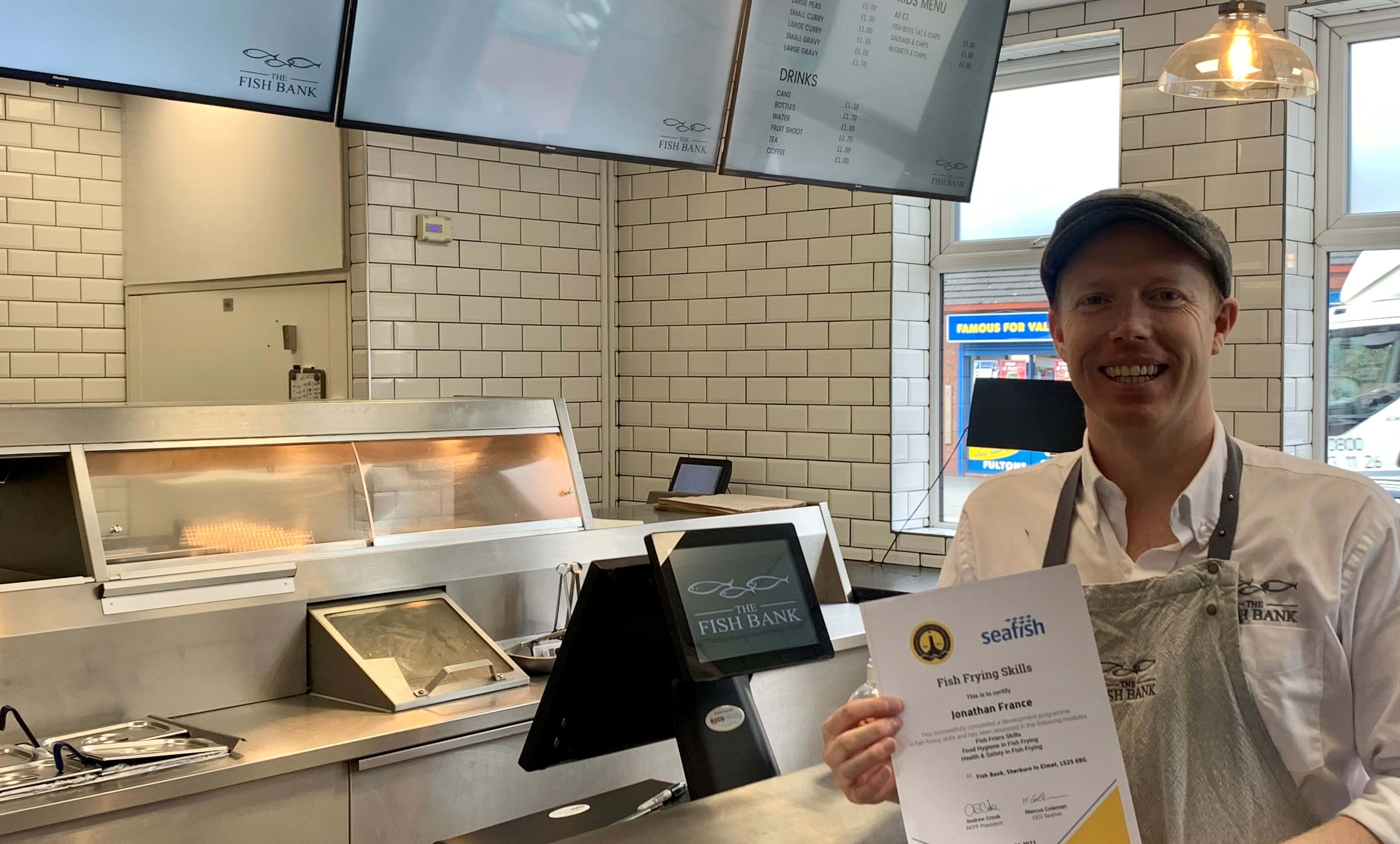 Jonathan France, fish frier, holding training certificate