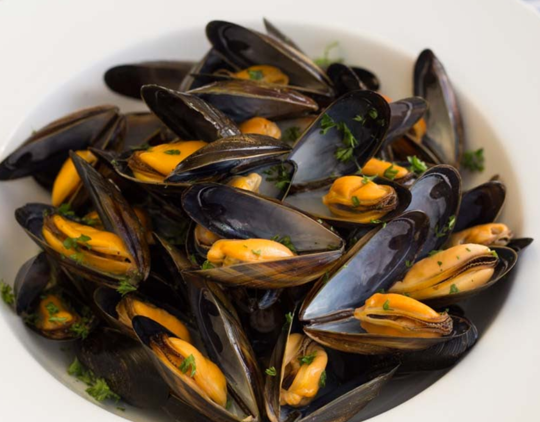 Mussels steamed open and presented in a bowl ready to eat.